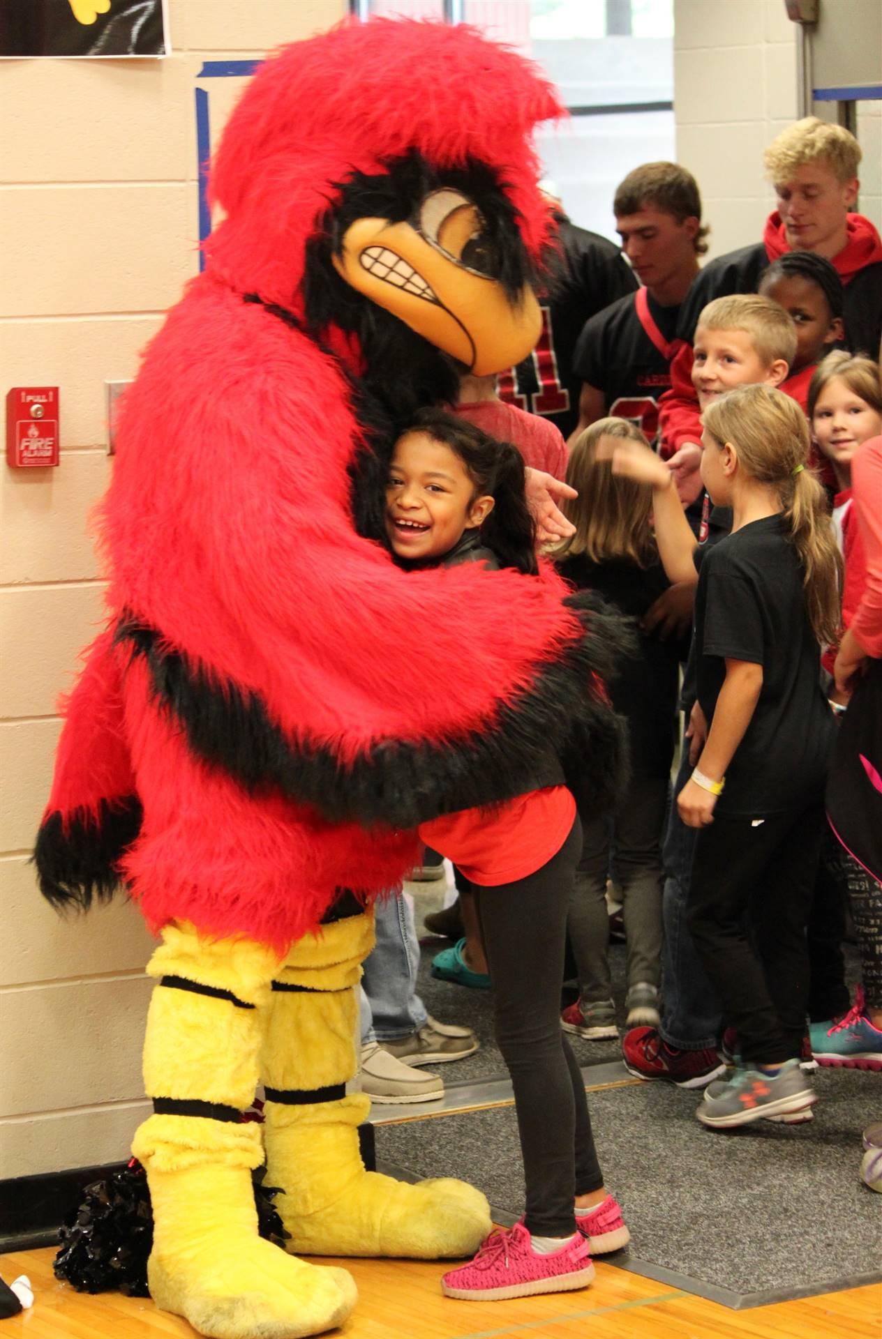 Elementary student hugging school mascot
