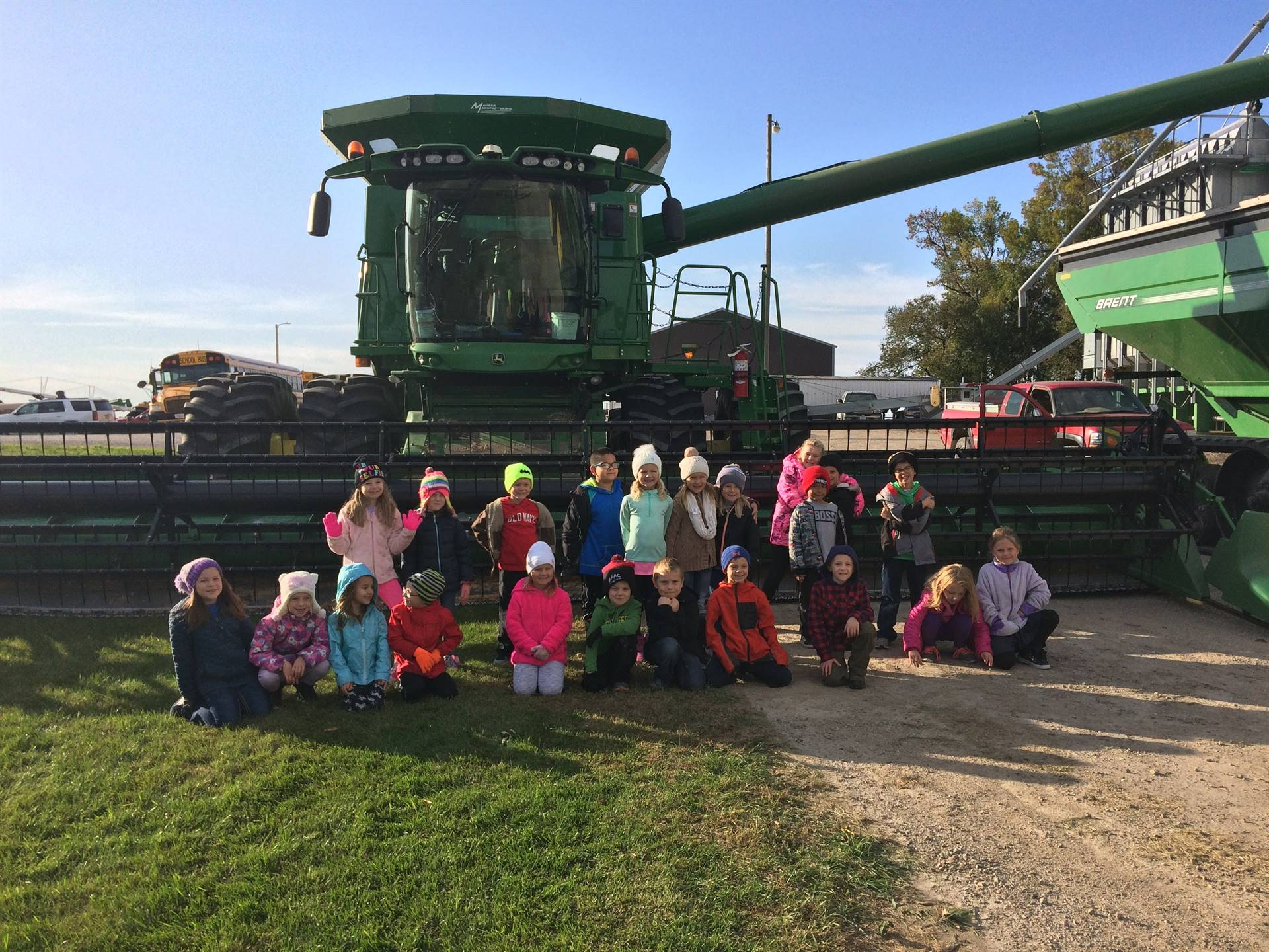 first grade class posing for a pic in front of a combine on a farm