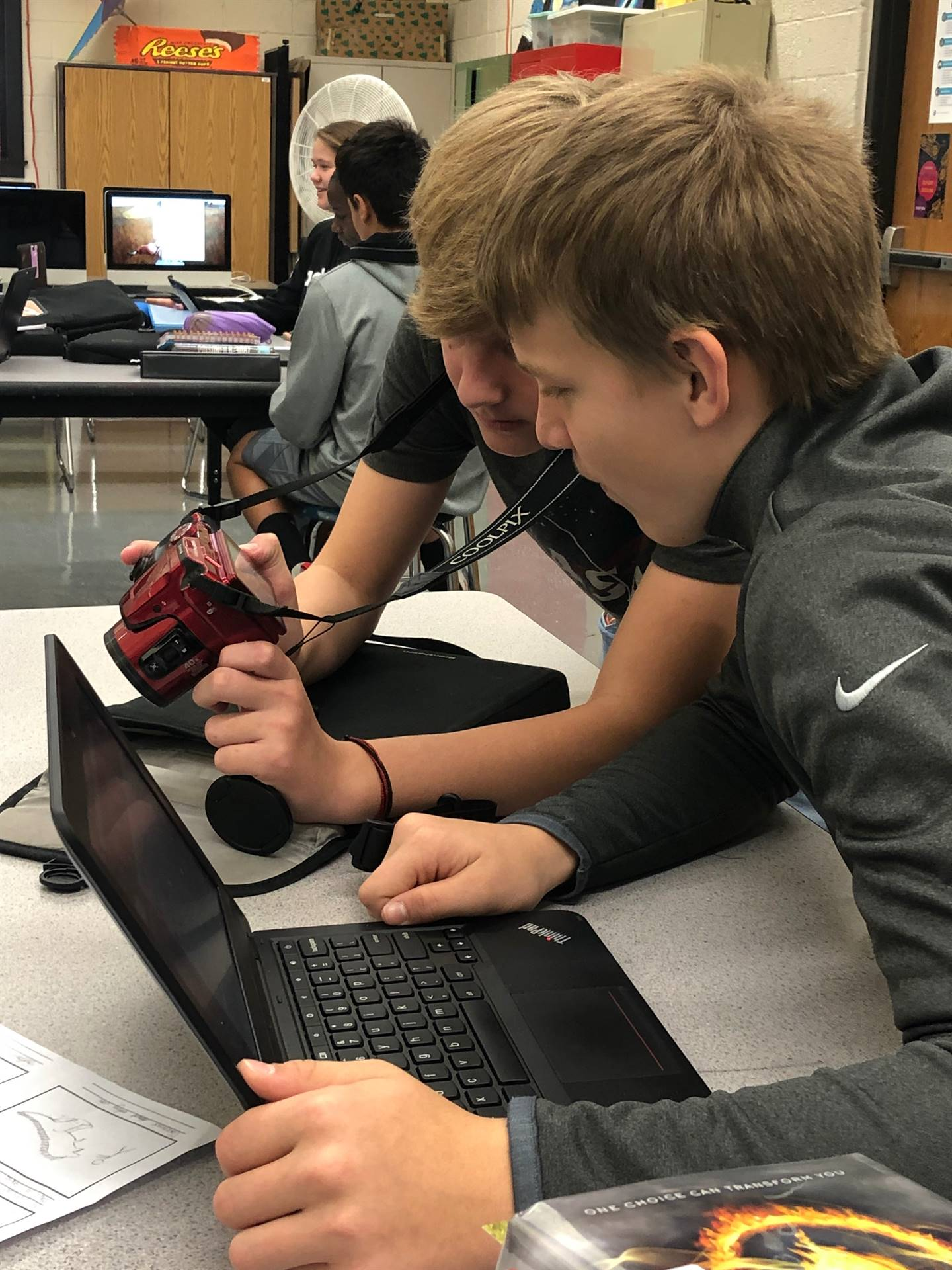 Two boys looking at a camera in a Middle School Digital Arts class