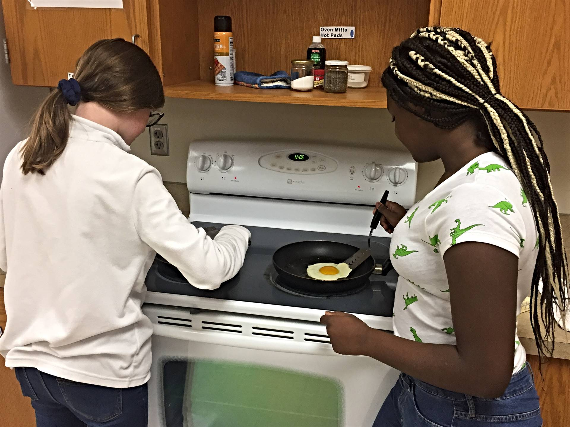 Two girls cooking eggs in an FCS class