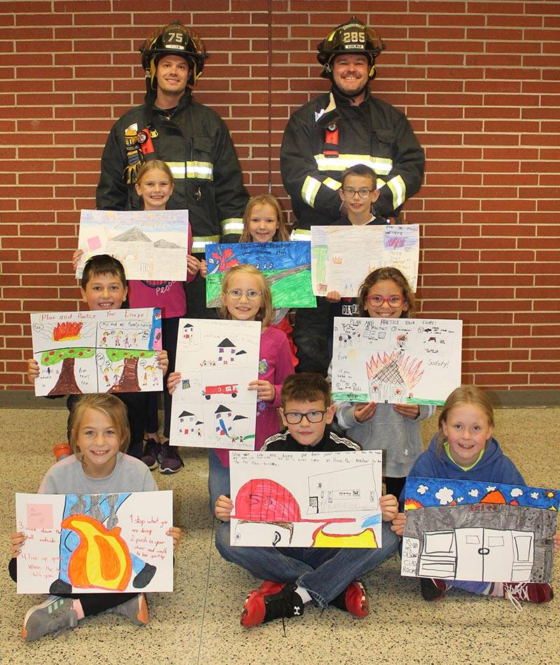 students holding fire prevention posters and 2 firemen