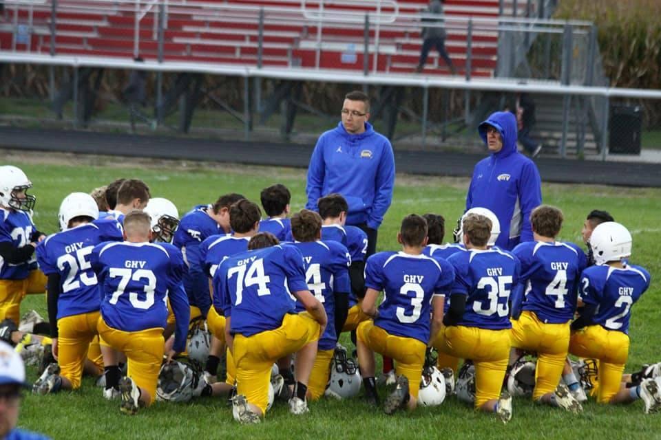 football players taking a knee as a group to listen to their coach