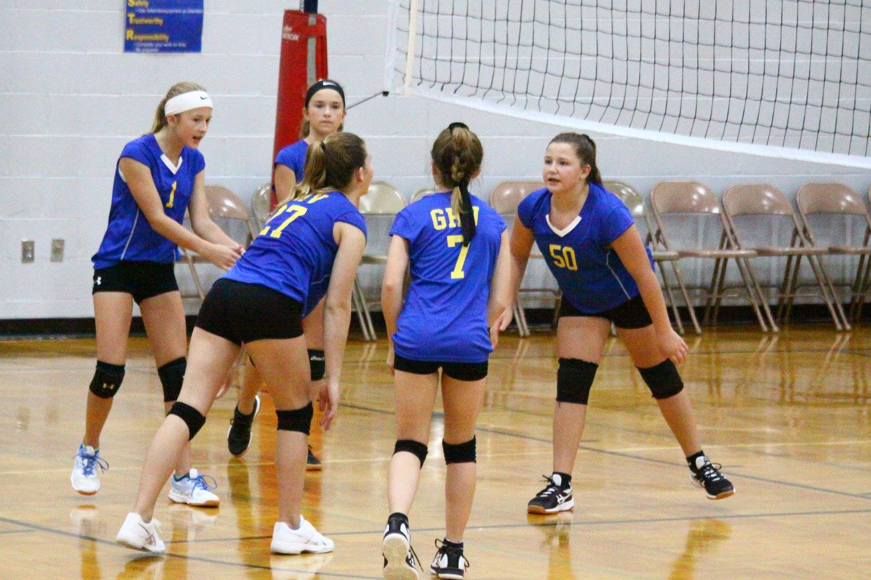 five volleyball players encouraging each other near the net
