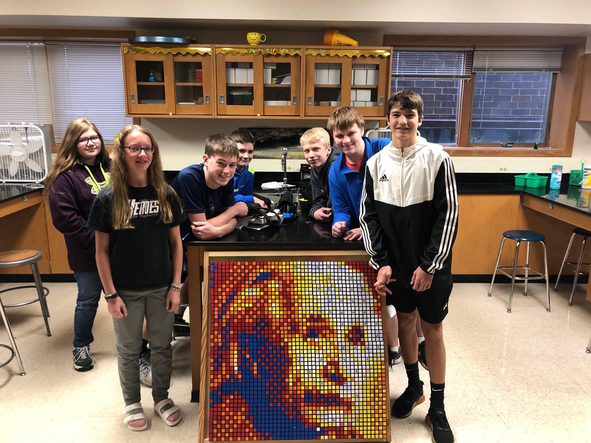 middle school students standing around a mosaic of Albert Einstein