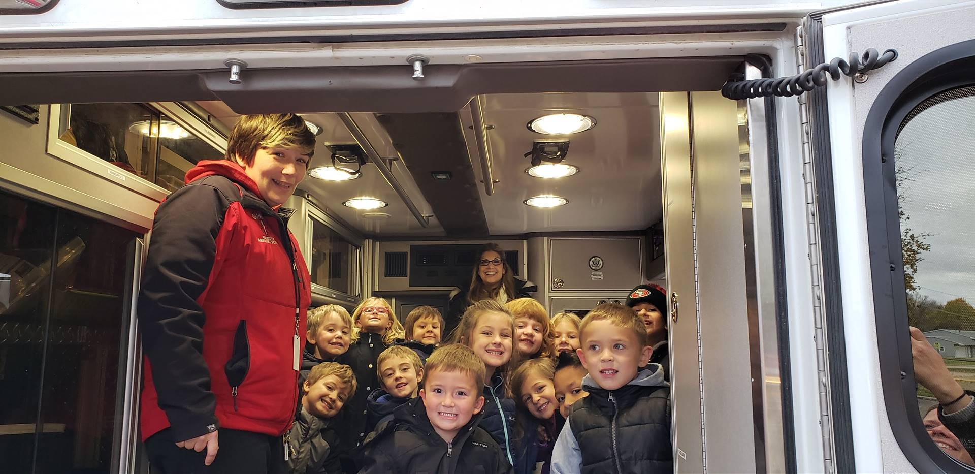 young elementary students in the back of an ambulance