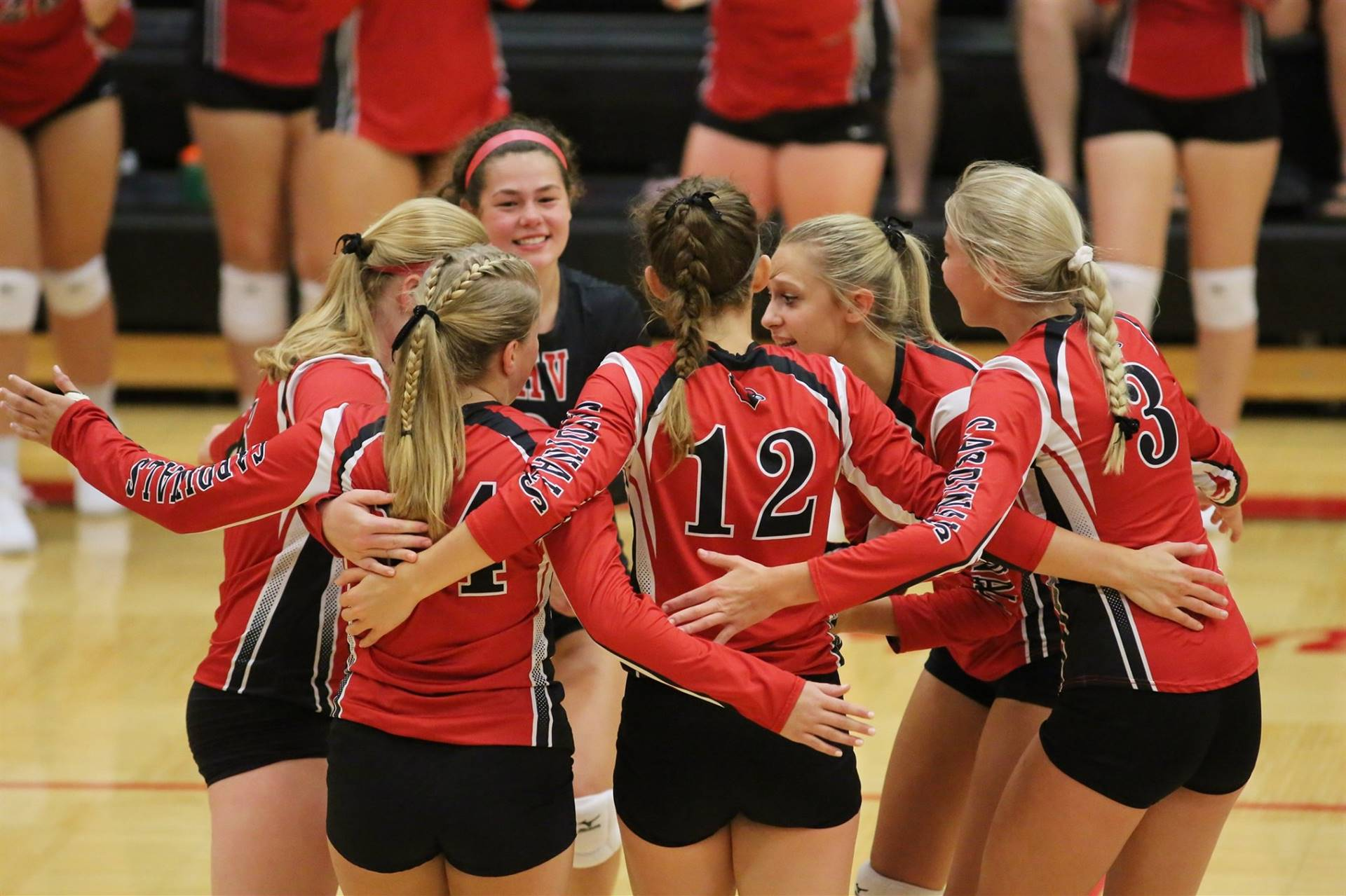 six volleyball players circling together in celebration of a point earned