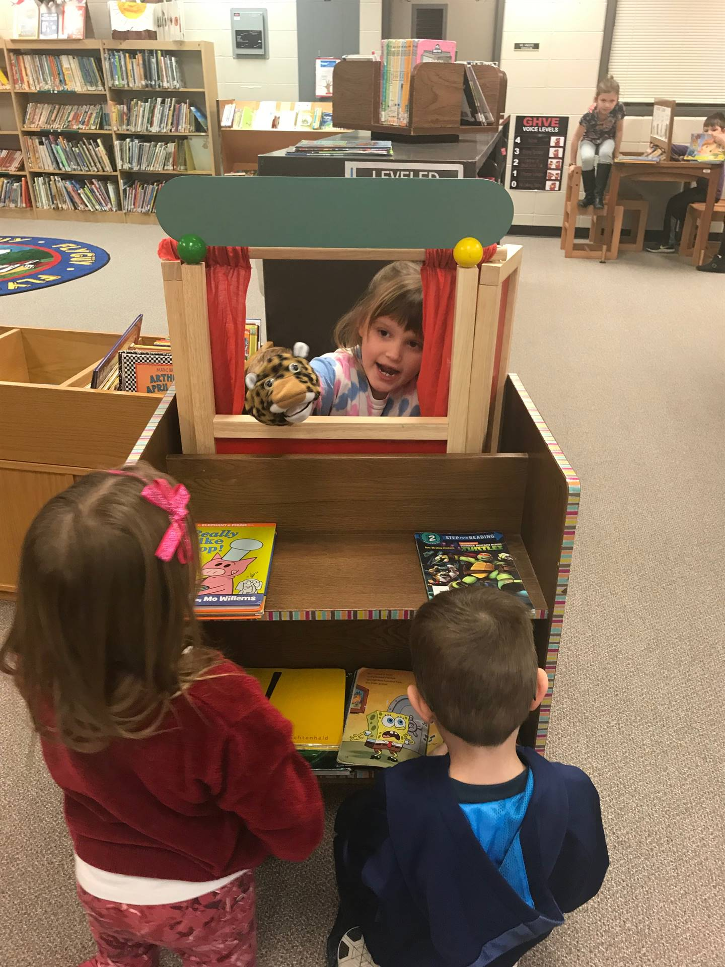 One student doing a puppet show for two other students
