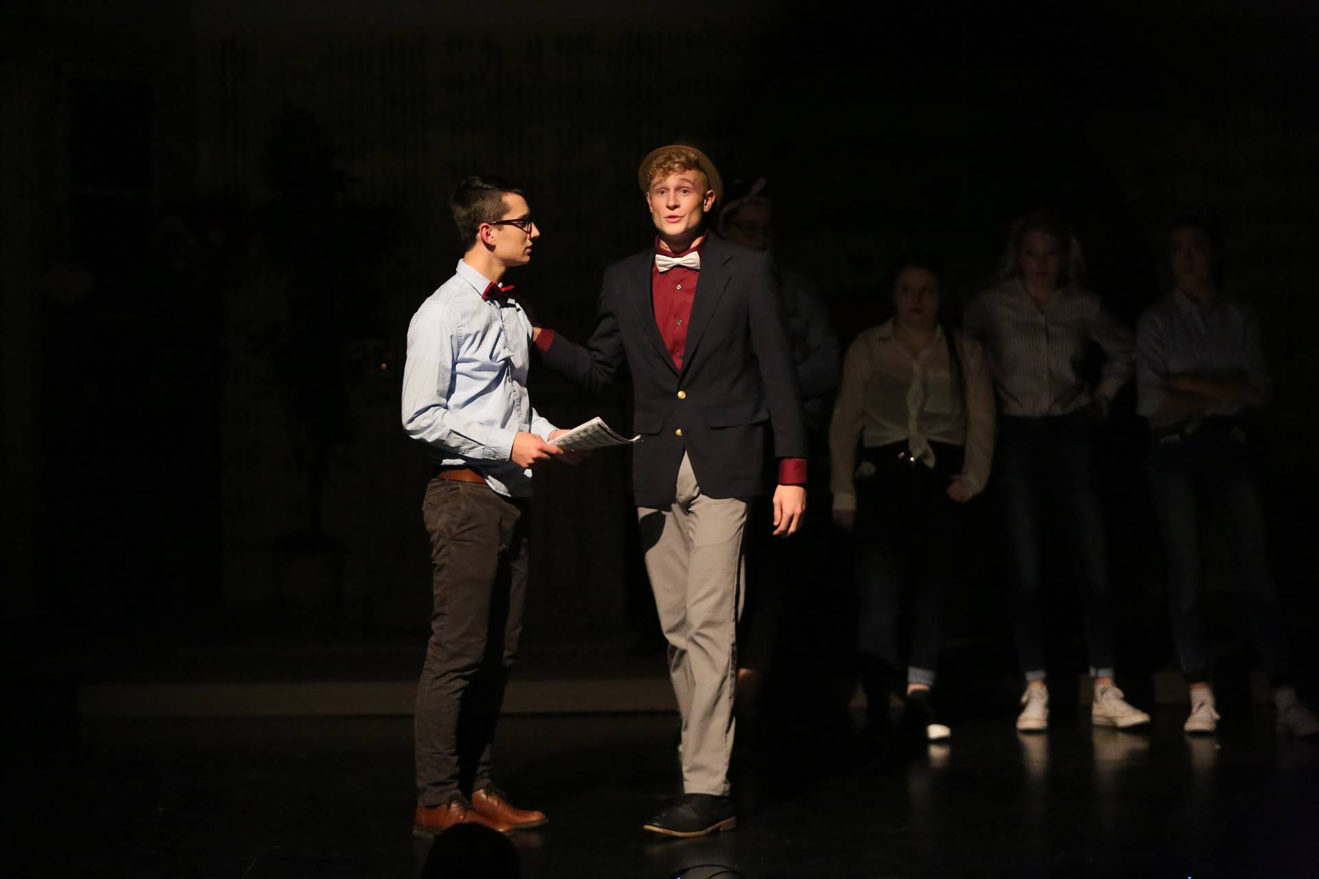 Two high school students on stage acting in a play