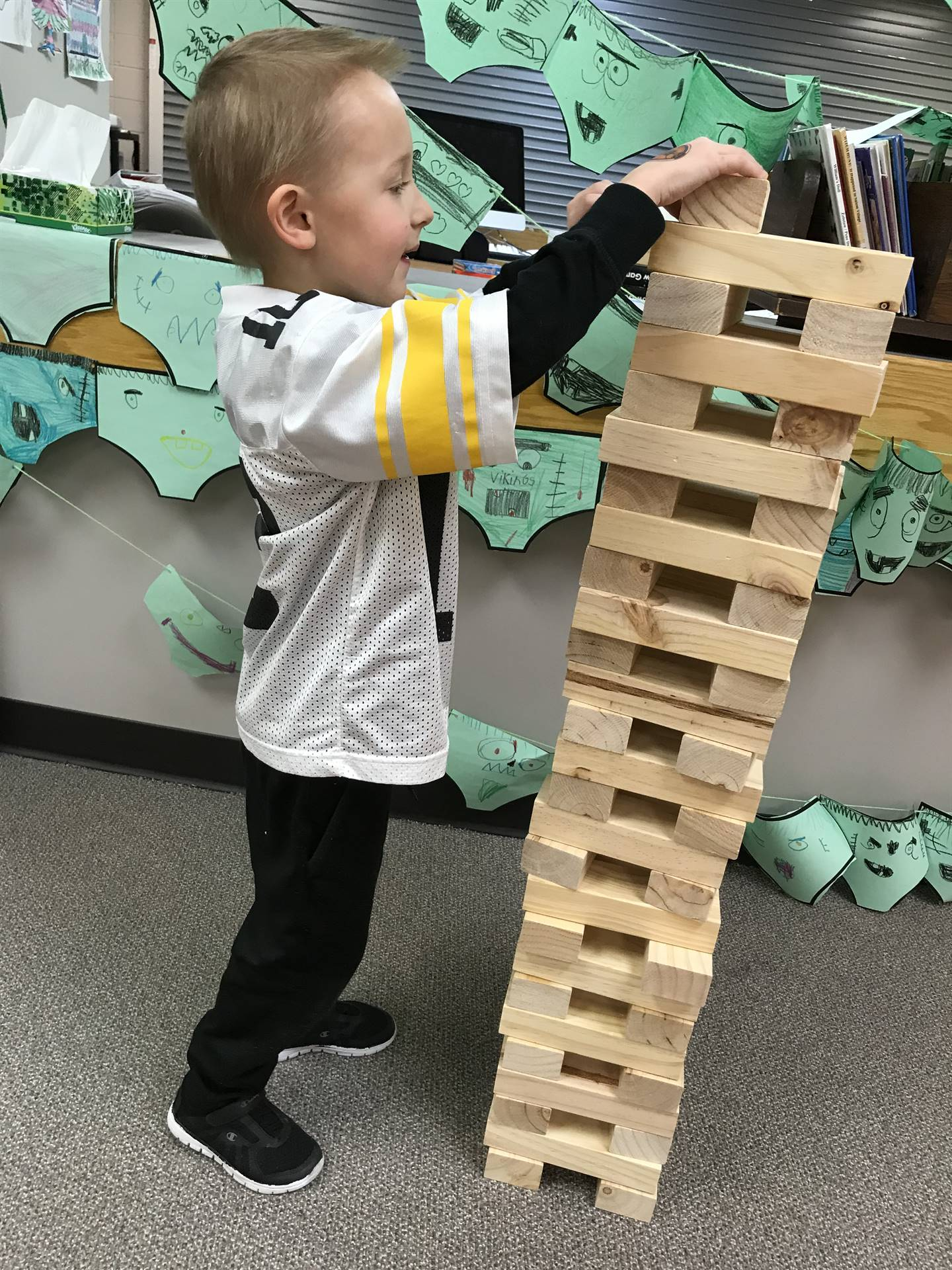 Elementary student playing large jenga in library
