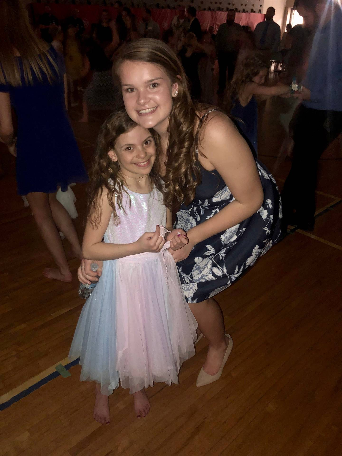 high school student with elementary student dressed up for a dance