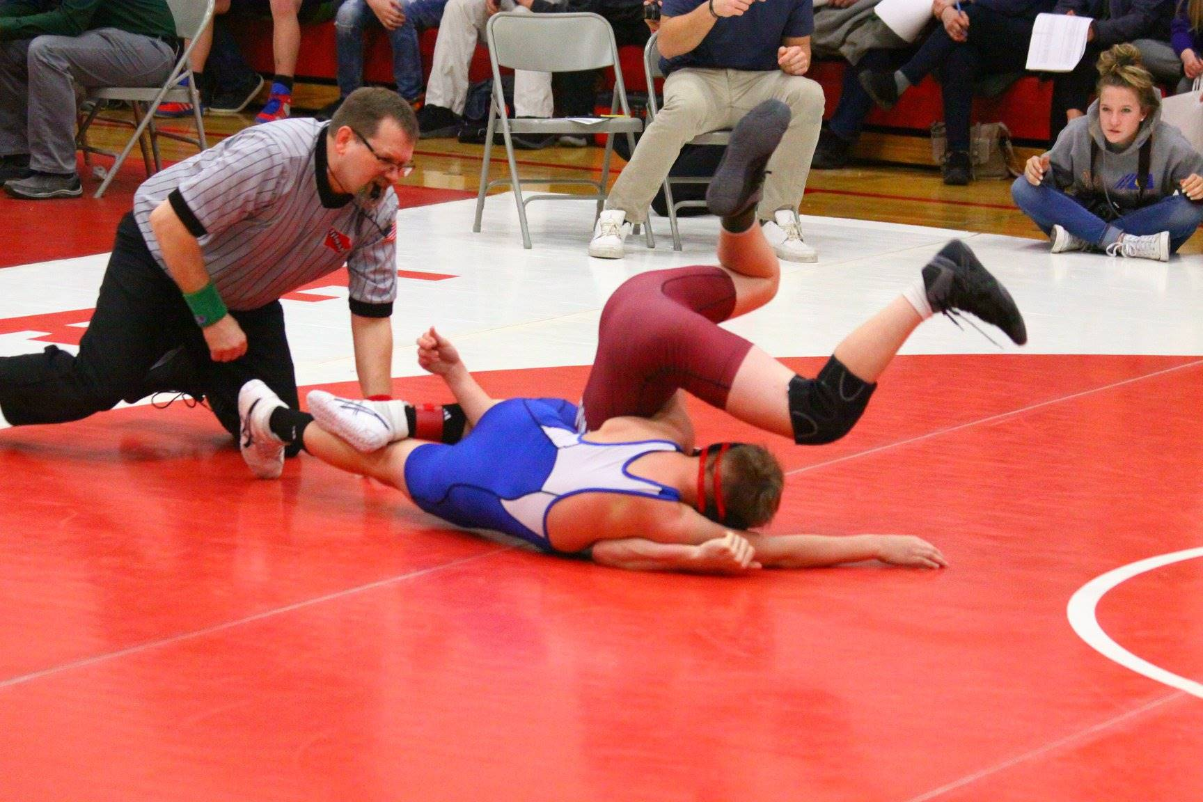 Two boys wrestling at a wrestling meet