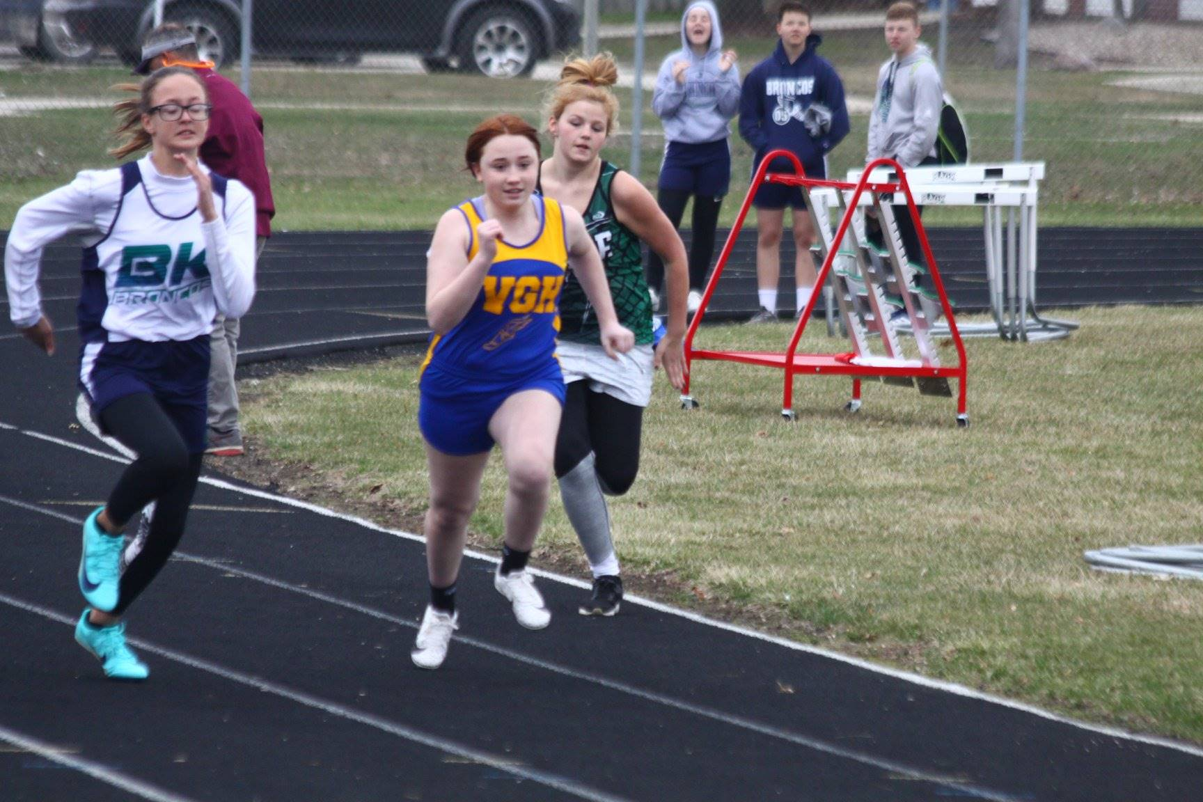 Three middle school girls running in a track meet