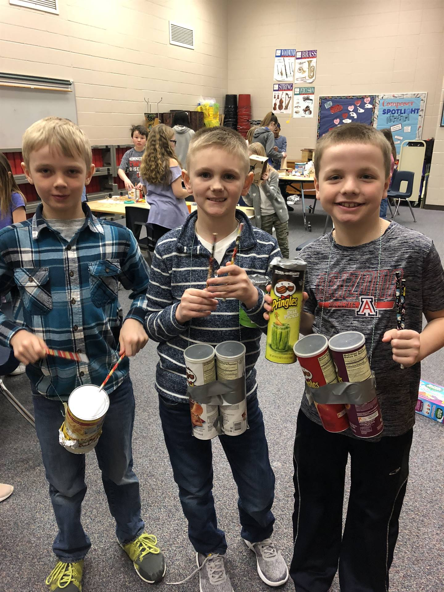 3 students posing for picture to show their homemade instruments