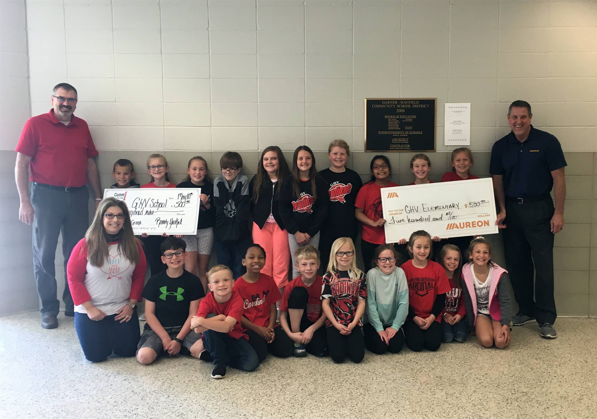 3rd grade students and teacher lined up in picture with grant checks from 2 businesses