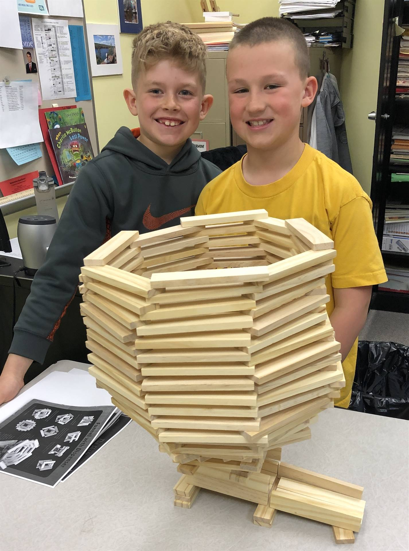 2 male students posing for picture with a building contraption in TAG class