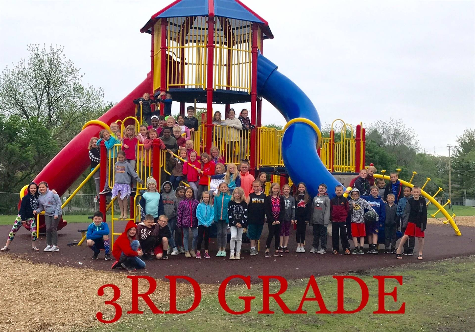 3rd grade children lined up on playground outside for class picture