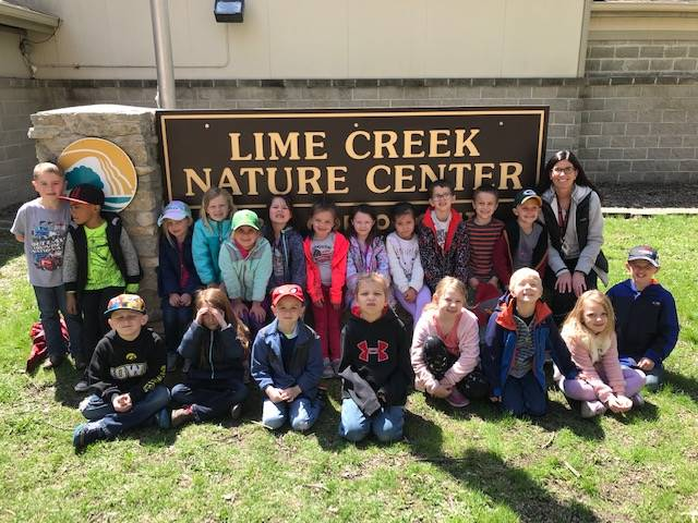 Students and teacher lined up for picture in front of nature center sign