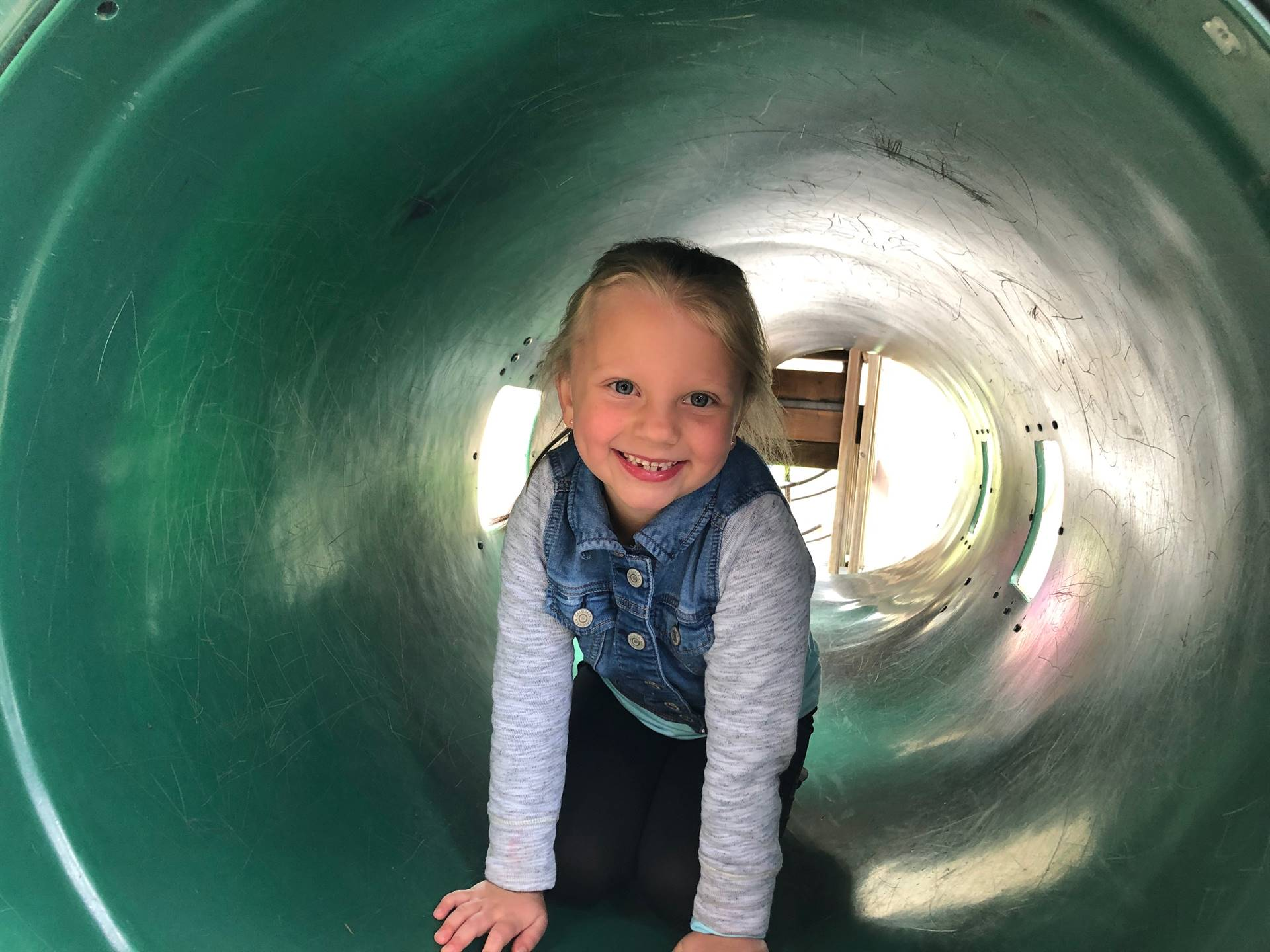 student posing in tunnel at a park