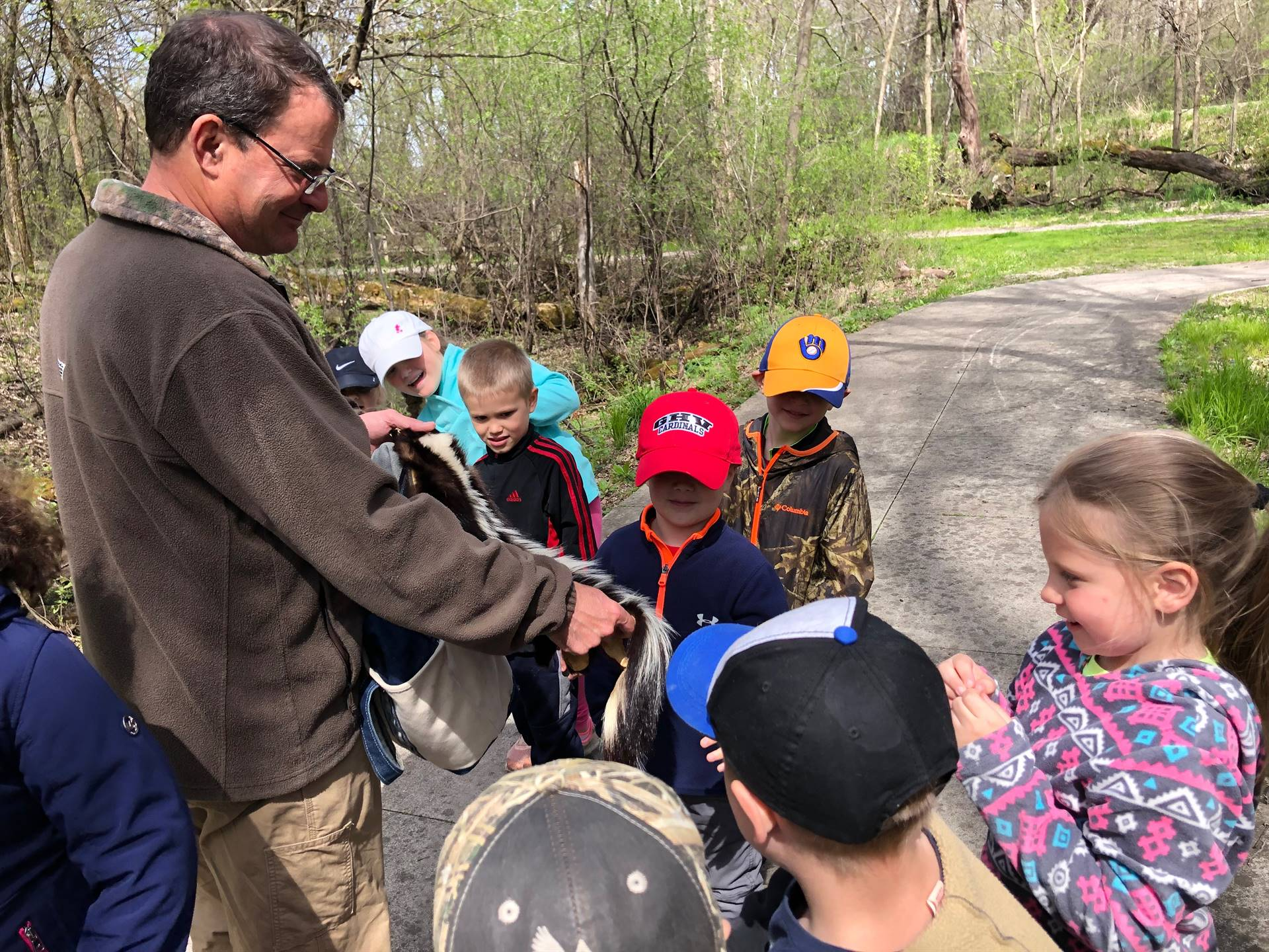 students with naturalist on field trip at nature center looking at a skunk hide
