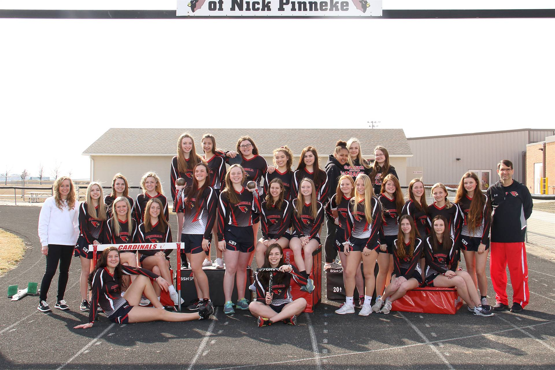 girls track team posing for a group picture on the track