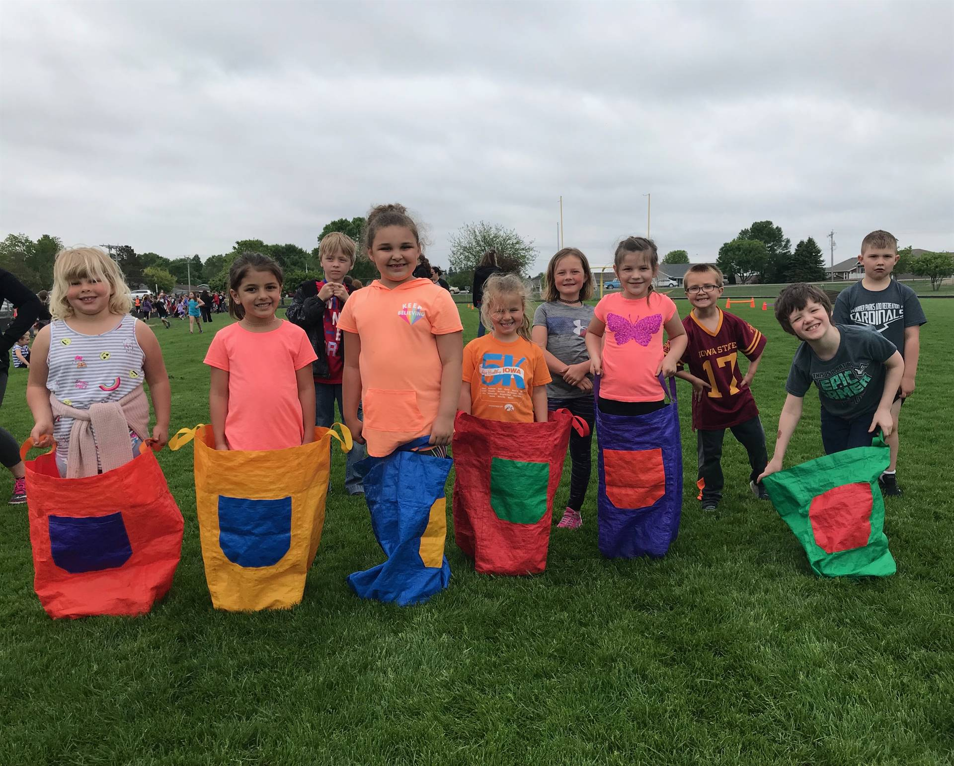 Students lined up in bean bag sacks at Track and Field Day for school