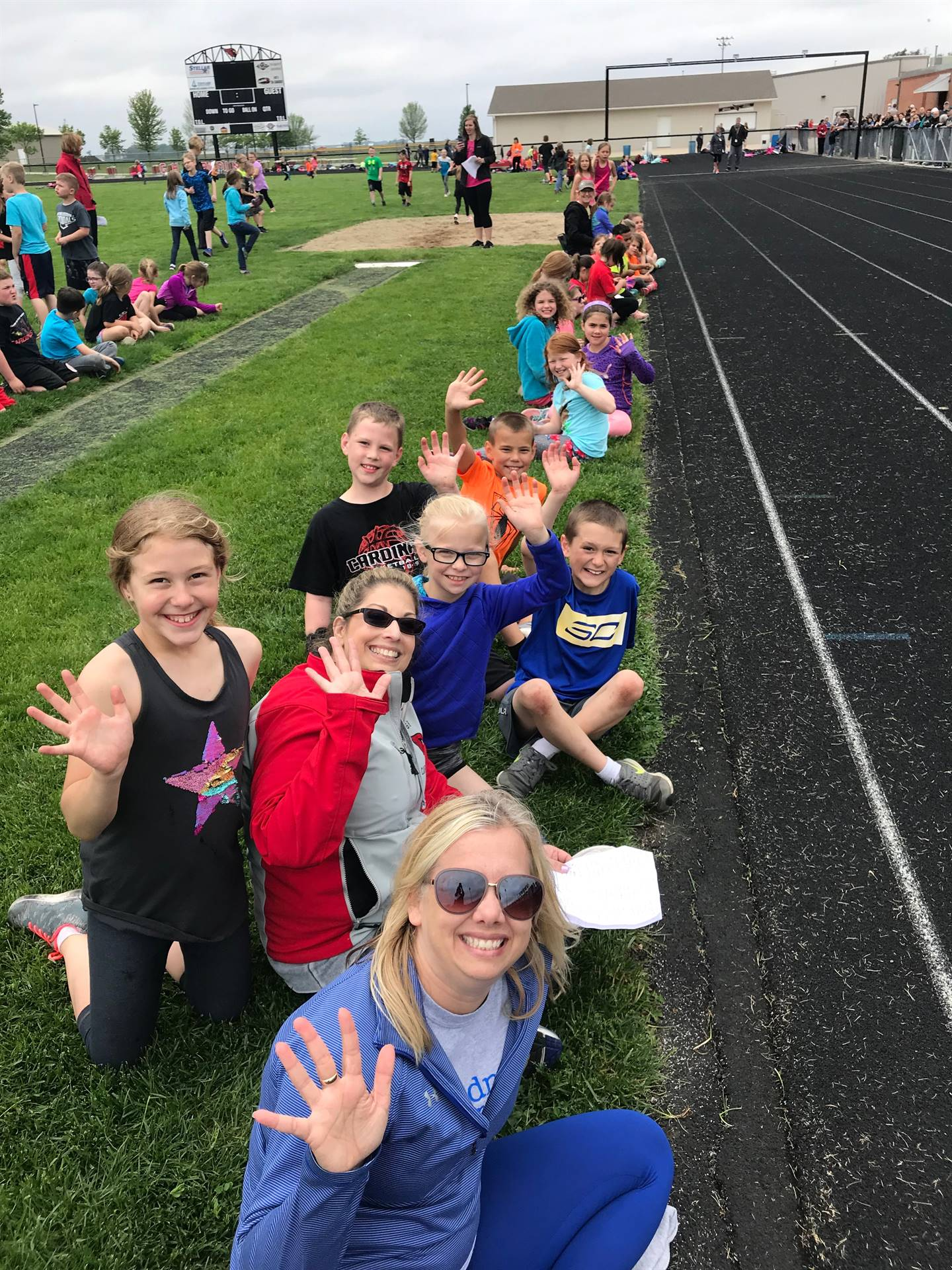 Students and Teacher sitting for picture by outside track