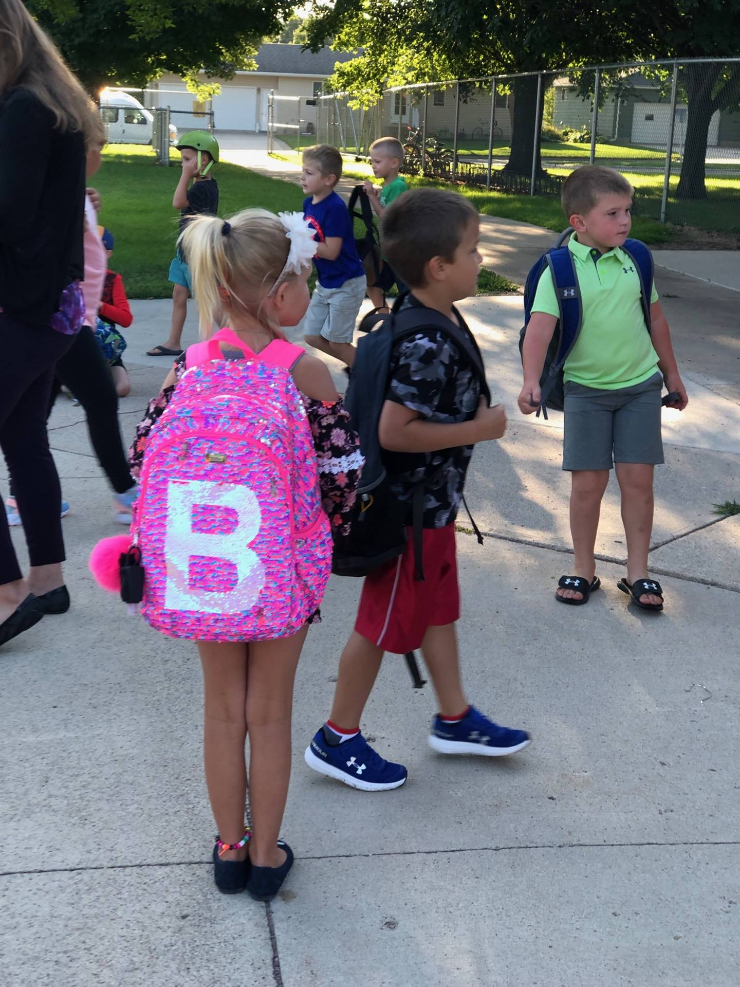 children standing with backpacks outside elementary school for first day