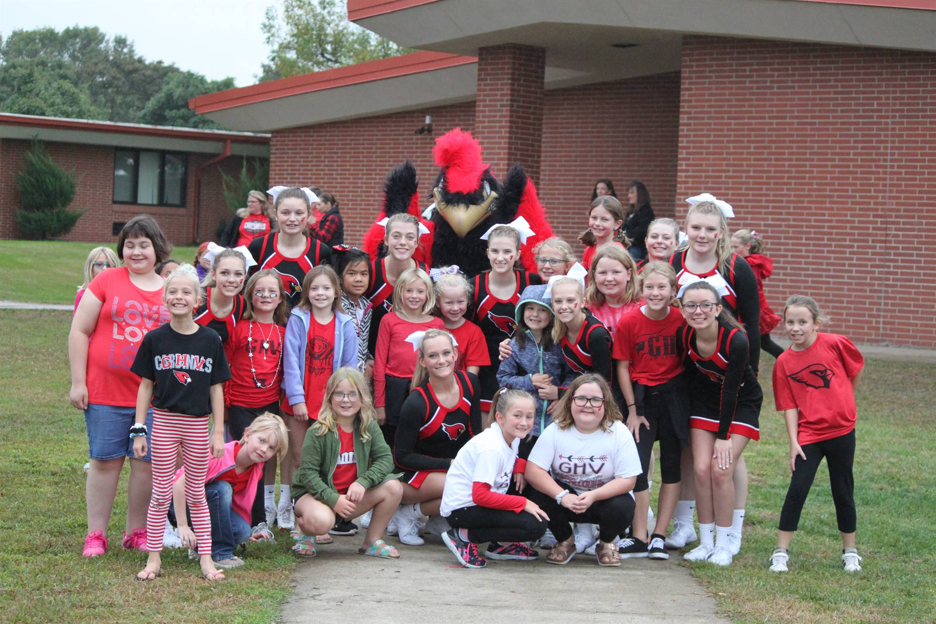 high school cheerleaders, mascot, and elementary girls posing for a on the playground