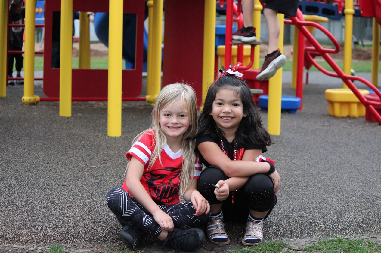 two elementary girls sitting on the ground of the playground