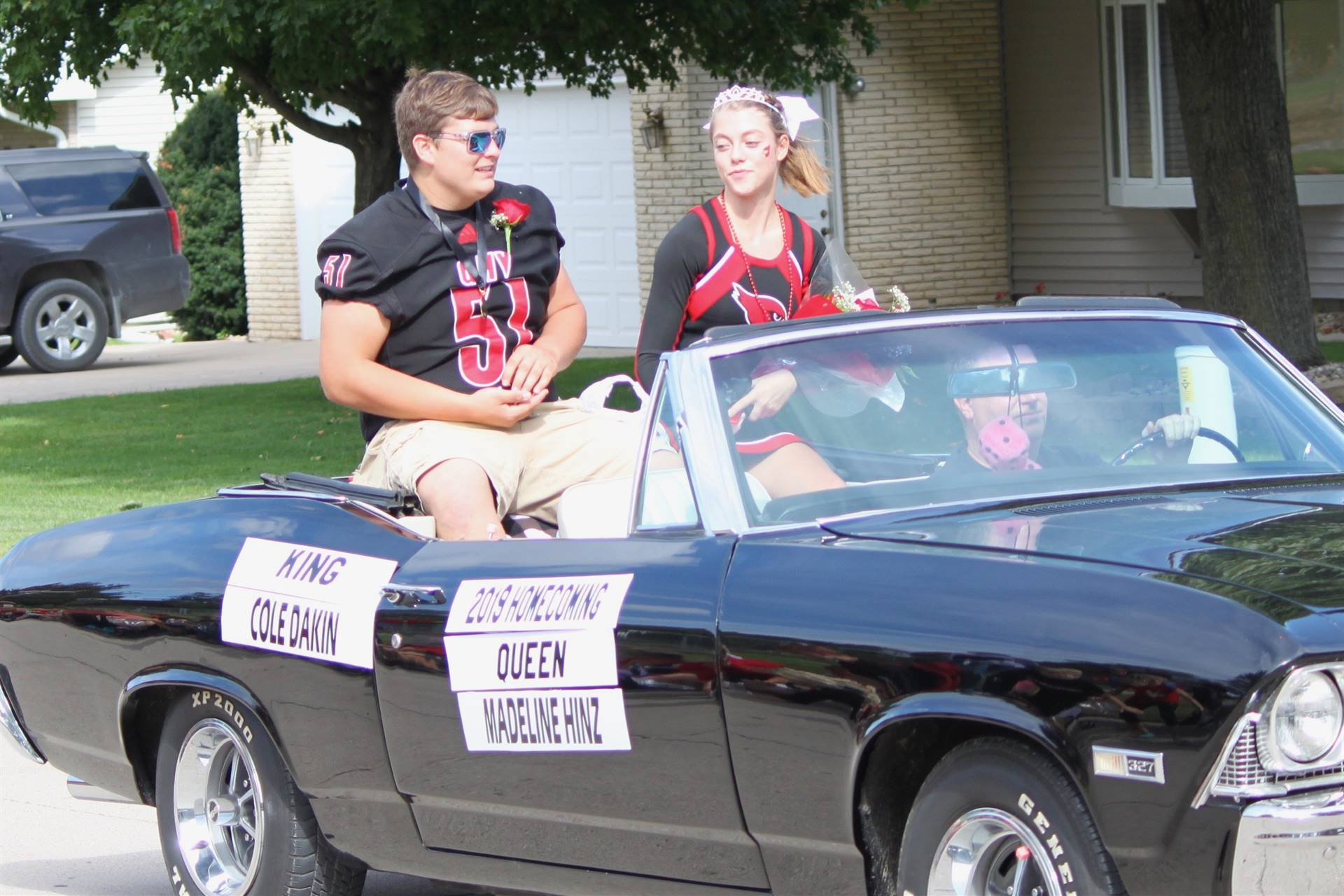 Homecoming king and queen riding in a convertible in parade
