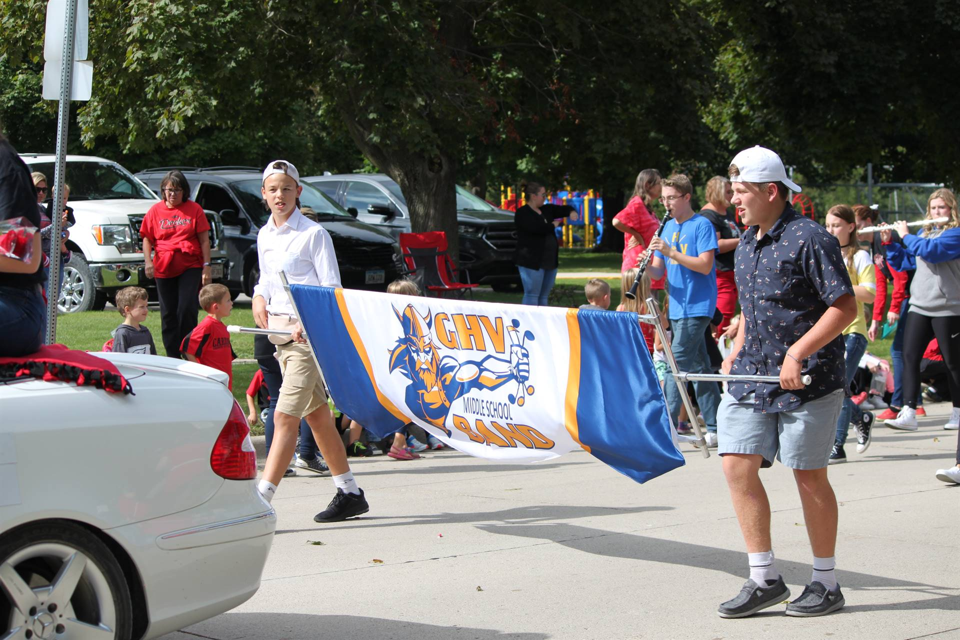 Two middle school students carrying GHV Band banner in homecoming parade
