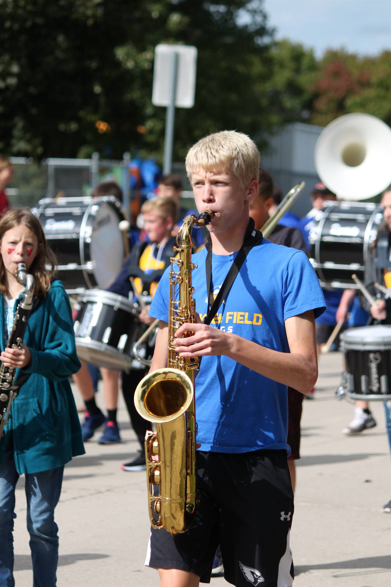 middle school student playing saxophone in homecoming parade