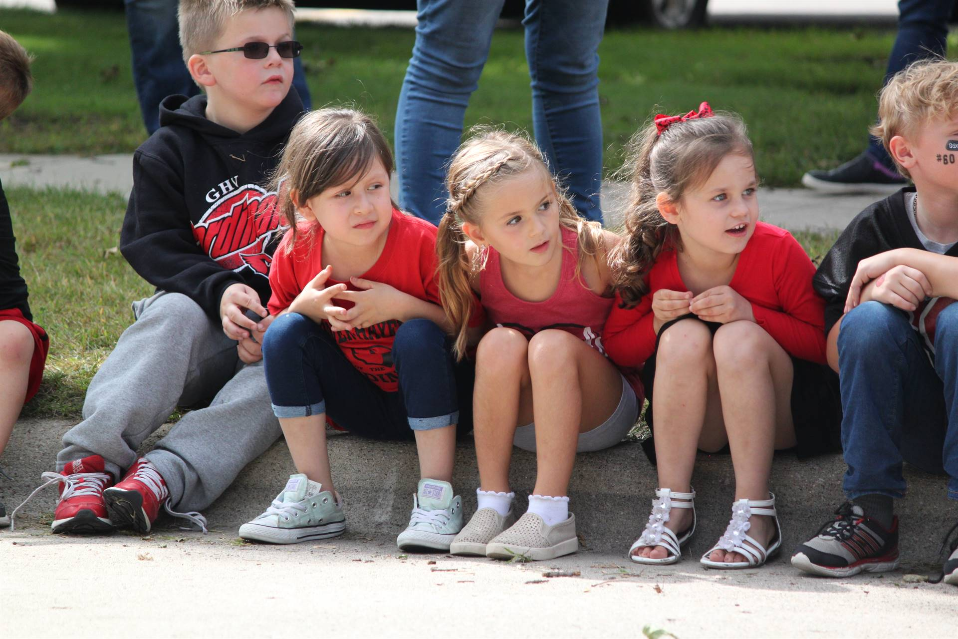 elementary students sitting on the curb waiting for the homecoming parade
