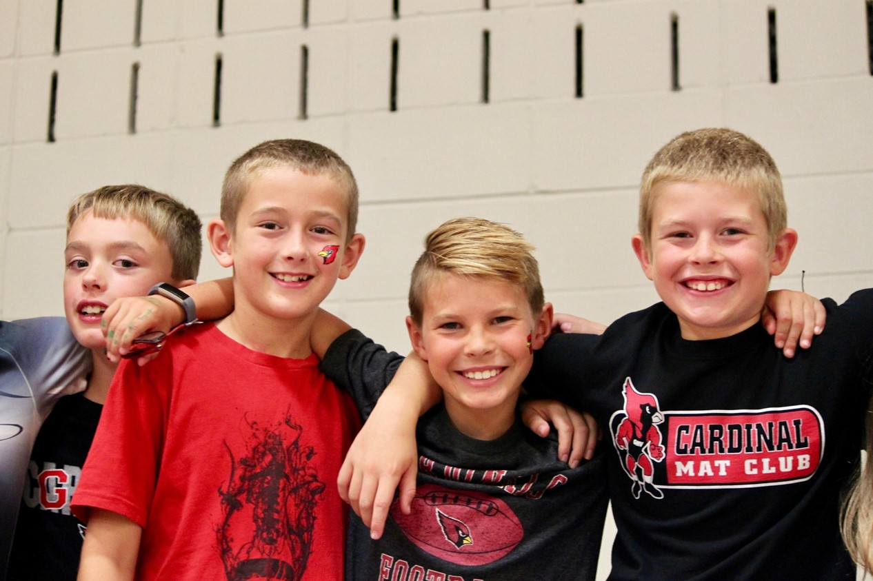 four elementary boys arm in arm in the gym watching the elementary homecoming pep rally