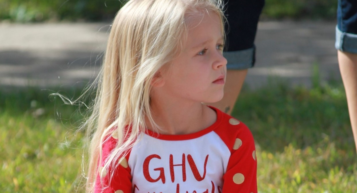 elementary girl sitting on curb watching homecoming parade