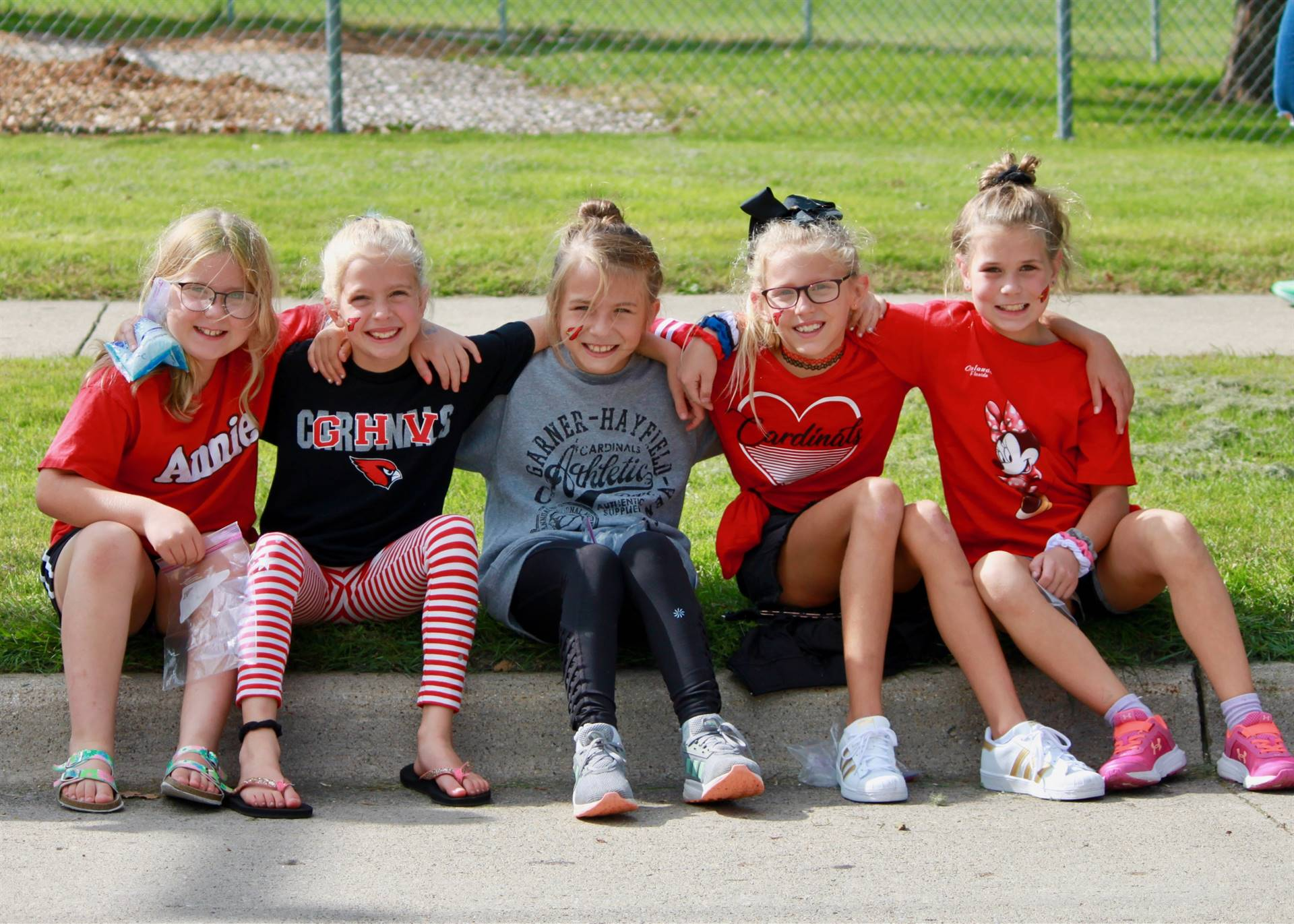 five elementary girls sitting on curb watching homecoming parade