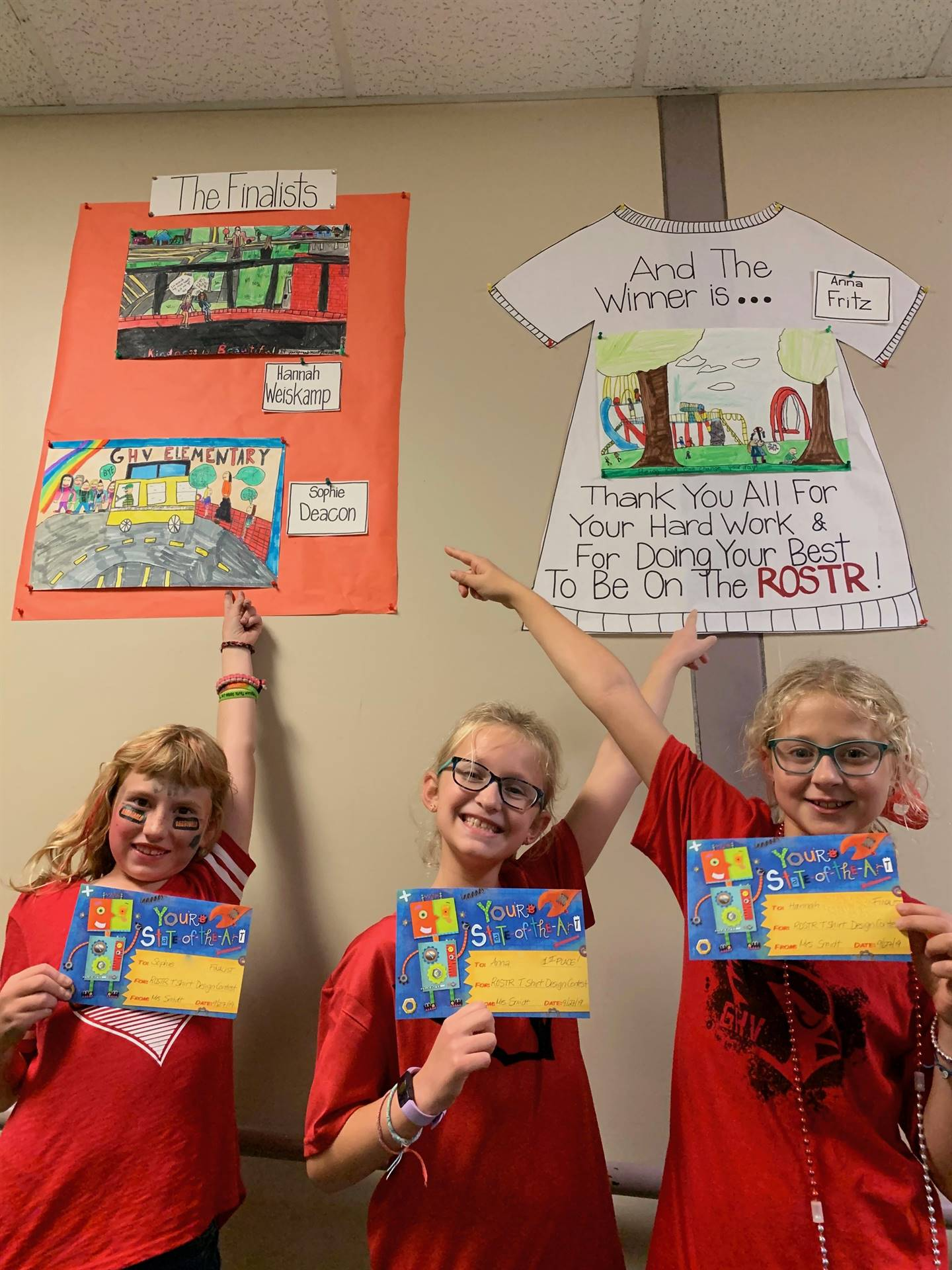 Three elementary girls holding certificates and pointing to their tshirt designs