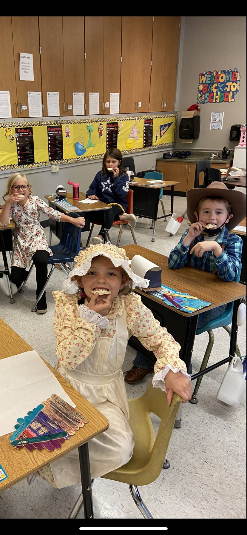 Second grade students dressed as pioneers in the classroom eating lunch
