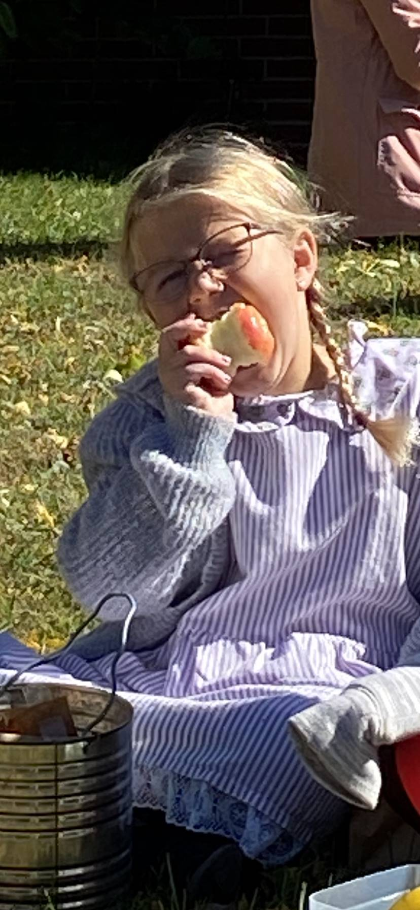 Second grade girl dressed as a pioneer outside eating an apple