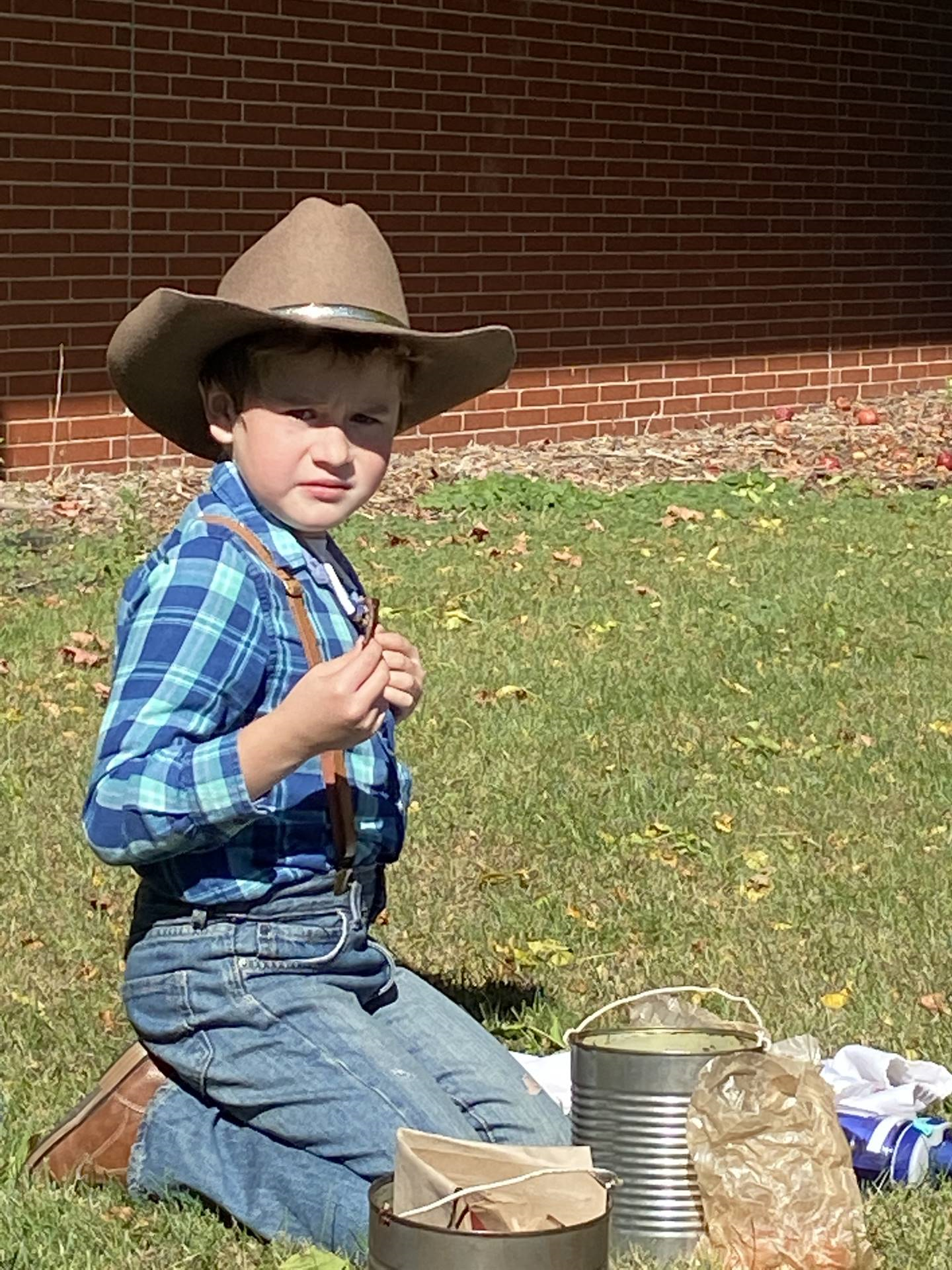 Second grade boy dressed as a pioneer outside eating lunch