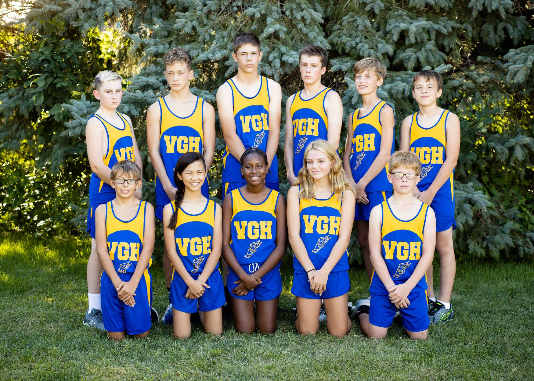 Group of 7th and 8th grade cross country runners lined up for team photo outside