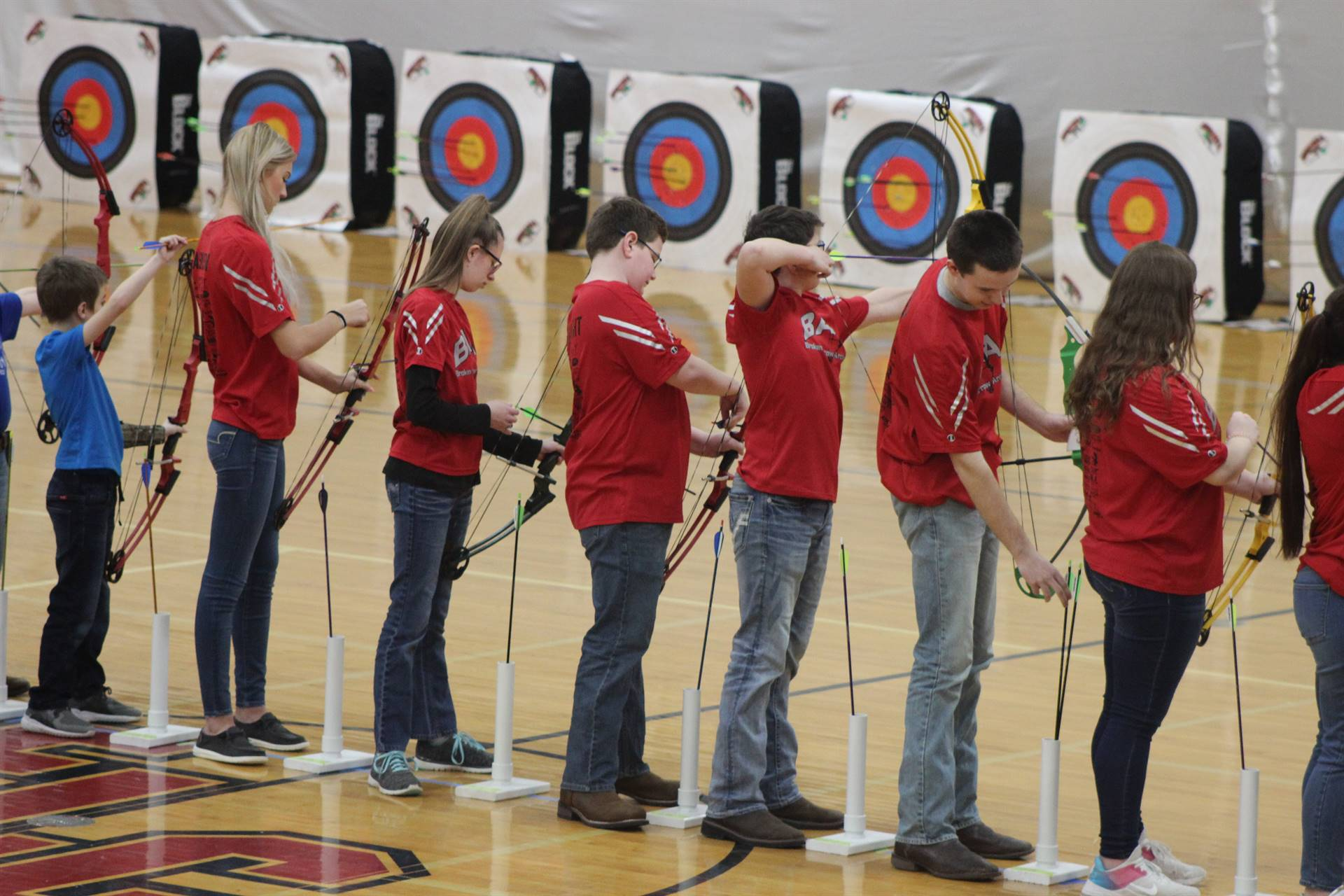 students lined up preparing to shoot arrows at targets in a gym