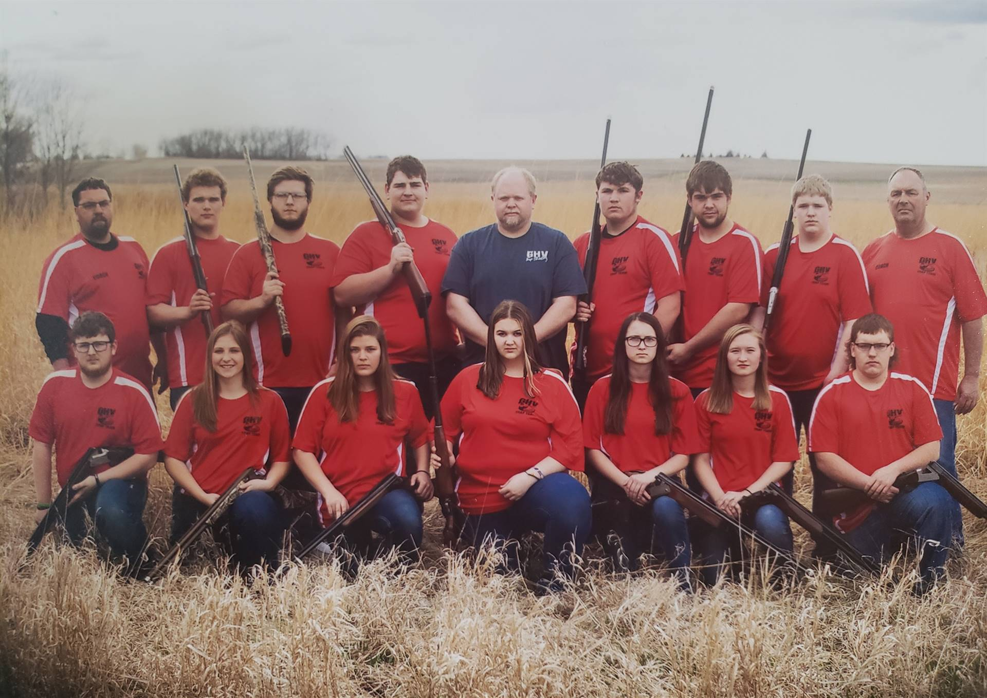 Trapshooting high school team posing for picture in a field