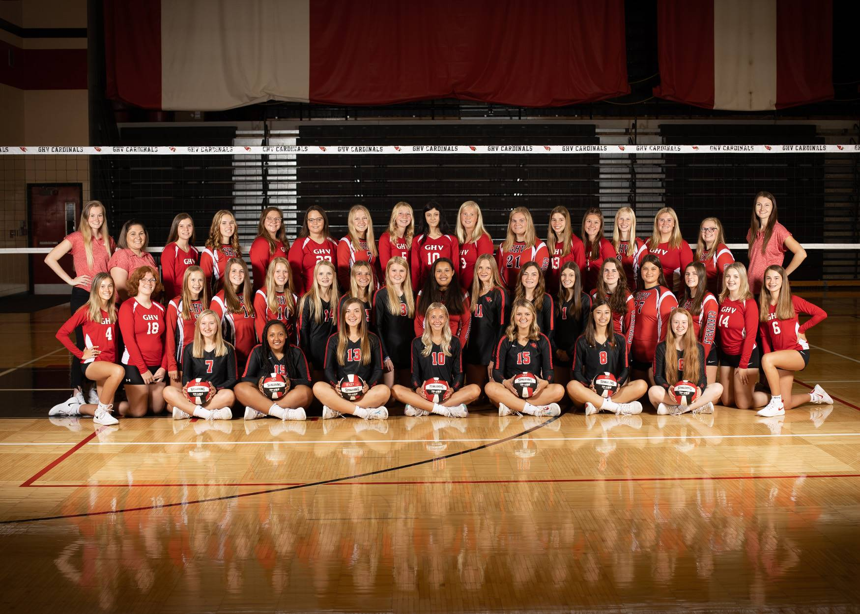 Girls volleyball players posing for a group photo