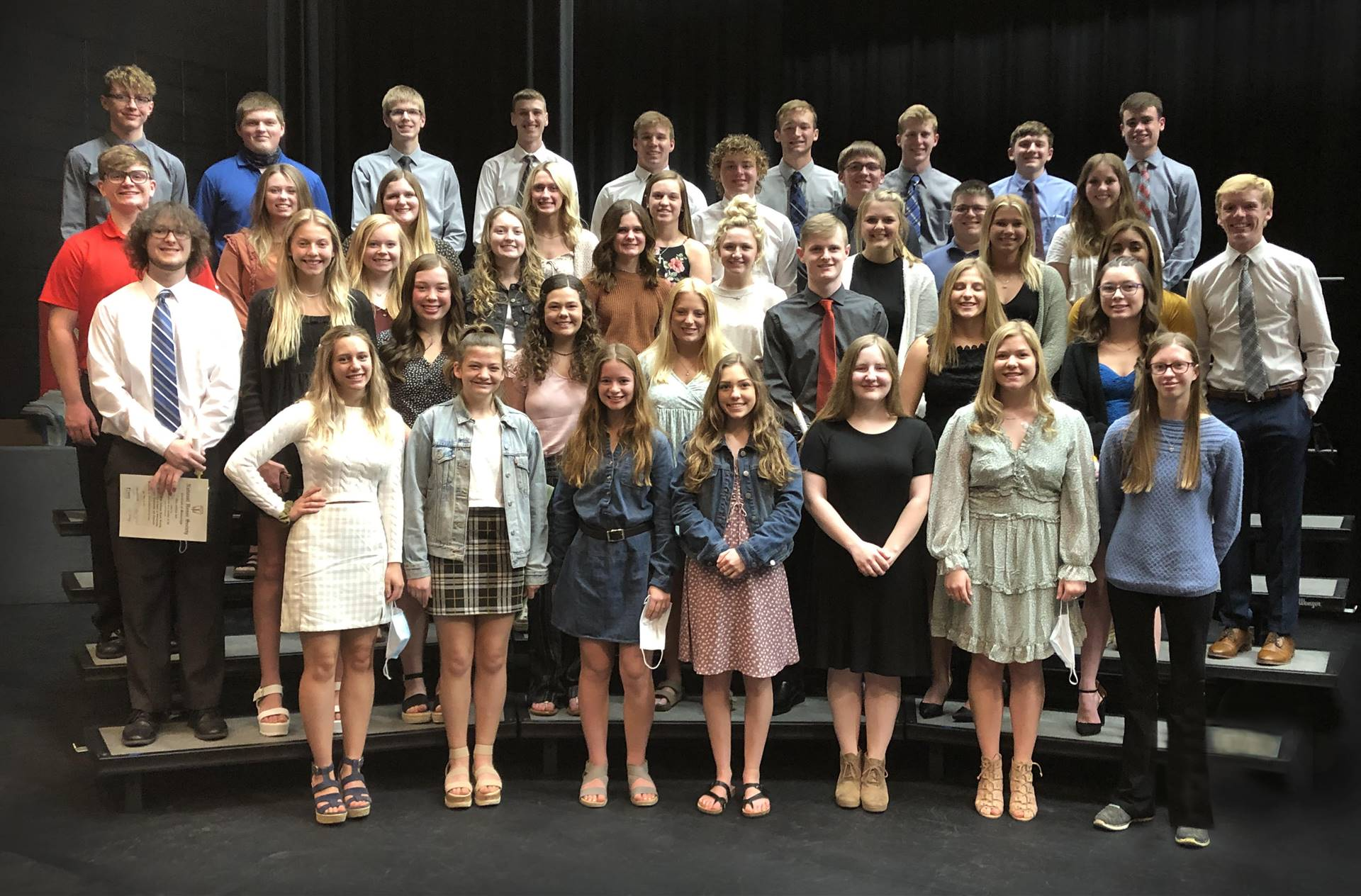 National Honor Society students posing for a group photo on risers